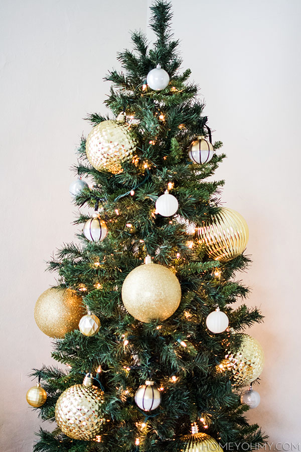 skinny christmas tree with large gold ornaments great for big impact in a small space - How To Decorate A Big Christmas Tree